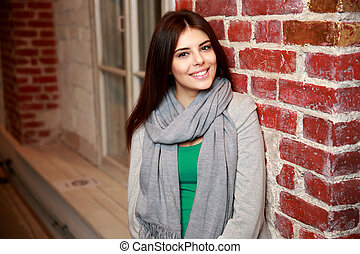 Young smiling woman leaning on the brick wall
