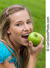 Young smiling woman looking at the camera while eating an apple