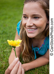 Young smiling woman looking away while lying in a park and holding a yellow flower