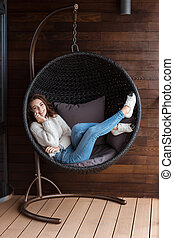 Young smiling woman lying in buble chair using smart phone -...