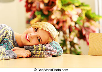 Young smiling woman lying on the table at home