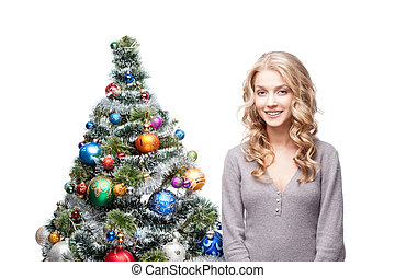 young smiling woman near christmas tree