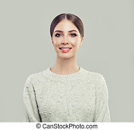 Young smiling woman on gray background, portrait