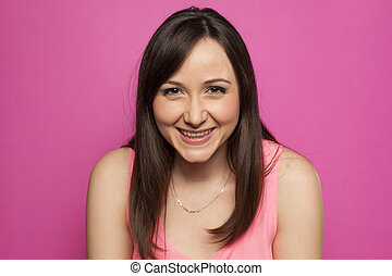 Young smiling woman on pink background