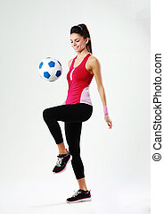 Young smiling woman playing with soccer ball on gray background