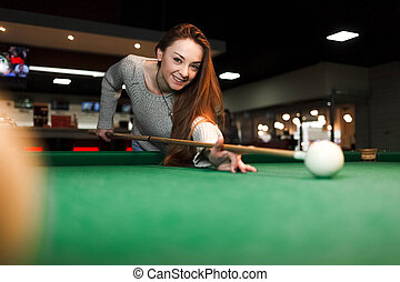 Young smiling woman plays billiards in a pub
