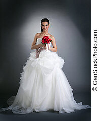 Young smiling woman posing in wedding dress