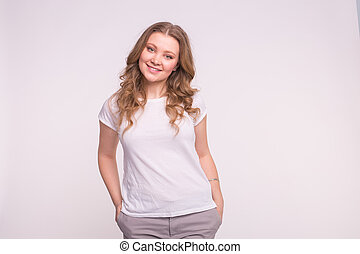Young smiling woman posing over white background with copy space