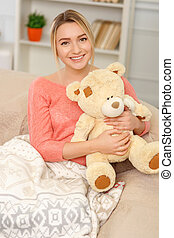 Young smiling woman posing with teddy bear.
