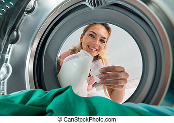 Smiling Woman Pouring Detergent In A Lid