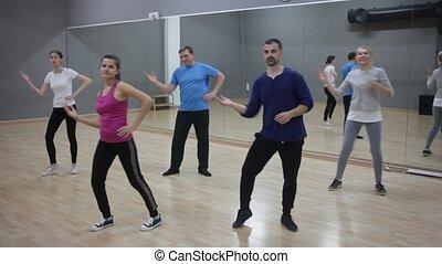 Portrait of dancing girl practicing vigorous swing during group training in dance studio
