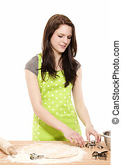 young smiling woman preparing christmas molds for baking with dough on white background