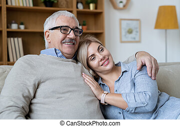 Young smiling woman putting head on shoulder of her senior father embracing her