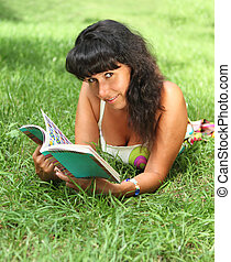 Young smiling woman reading in summer park