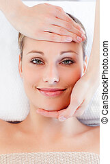Young smiling woman receiving a head massage