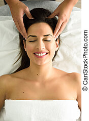 Young smiling woman receiving a head massage in a spa...