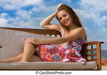 young smiling woman relaxing on natural background