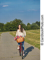 Young smiling woman rides a bicycle with a basket full of flowers in countryside