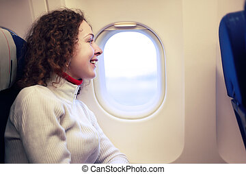 Young smiling woman sits in a chair near the illuminator of the airplane.
