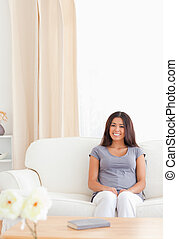 young smiling woman sitting on a sofa
