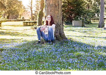 young smiling woman sitting on a spring flower meadow