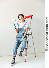 Young smiling woman sitting on ladder