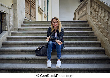 Young smiling woman sitting on steps