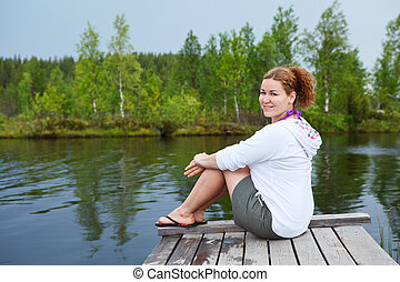 Young smiling woman sitting on wooden boards on pond edge