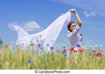 Young smiling woman standing in yellow wheat field holding a white long piece of cloth in the wind.