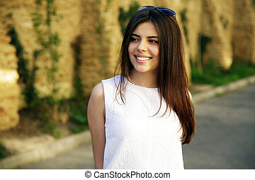 Young smiling woman standing outdoors