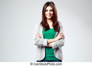 Young smiling woman standing with arms folded on gray background