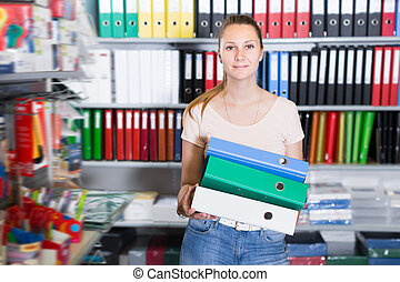 Young smiling woman standing with folders