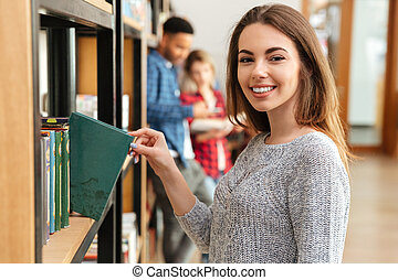 Young smiling woman student standing in library holding book