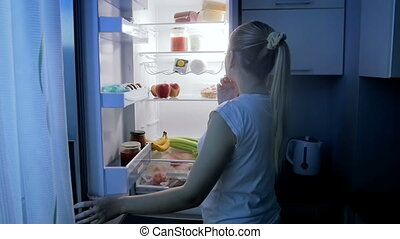 Young smiling woman taking food from refrigerator at night
