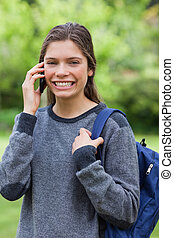 Young smiling woman talking with her mobile phone while standing in the countryside