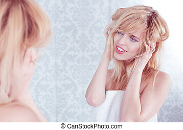 Young Smiling Woman Tousling Hair in Mirror