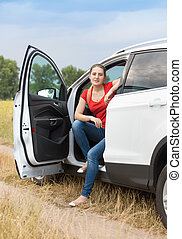 Young smiling woman traveling by car at countryside opened door and looking in camera