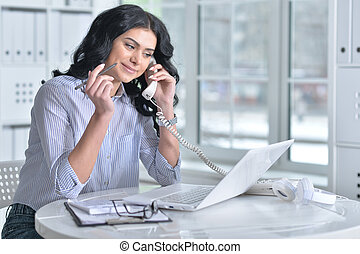 woman using laptop and talking on phone