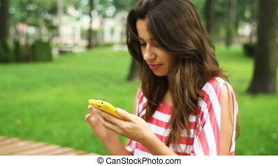 Young smiling woman using smartphone sitting on bench in park