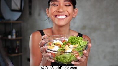 Young smiling woman vlogger talking, showing healthy salad...