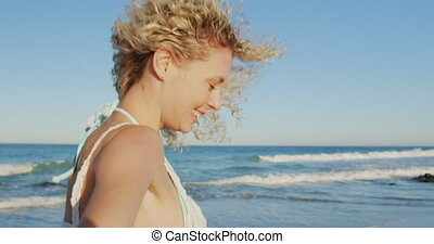 Young smiling woman walking on a beach 4k