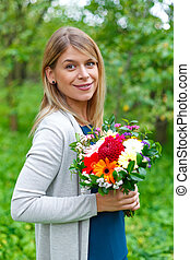 Young smiling woman with a bouquet of flowers
