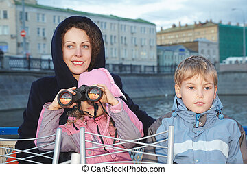 Young smiling woman with children stand on the background of water and buildings
