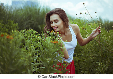 Young smiling woman with closed eyes in nature