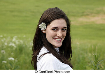 Young smiling woman with flower in hair