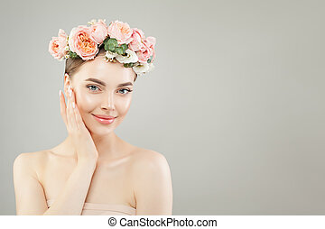 Young smiling woman with healthy skin and pink roses flowers on gray background
