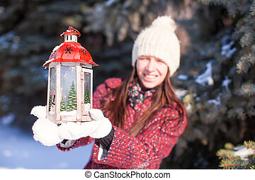 Young smiling woman with red Christmas lantern in winter forest