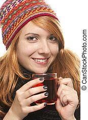 young smiling woman with winter cap warming-up with tea on white background
