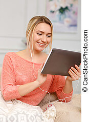 Young smiling woman working on the tablet.