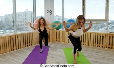Young smiling women doing fitness. Squating holding a stick....